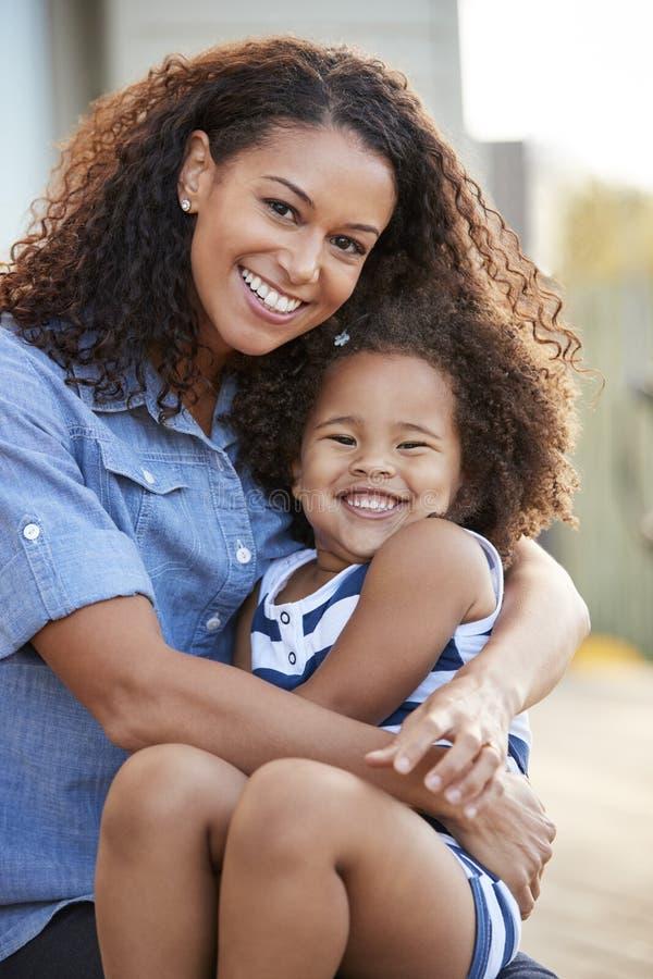 Modern för det blandade loppet och barndottern ler till kameran utanför royaltyfria foton