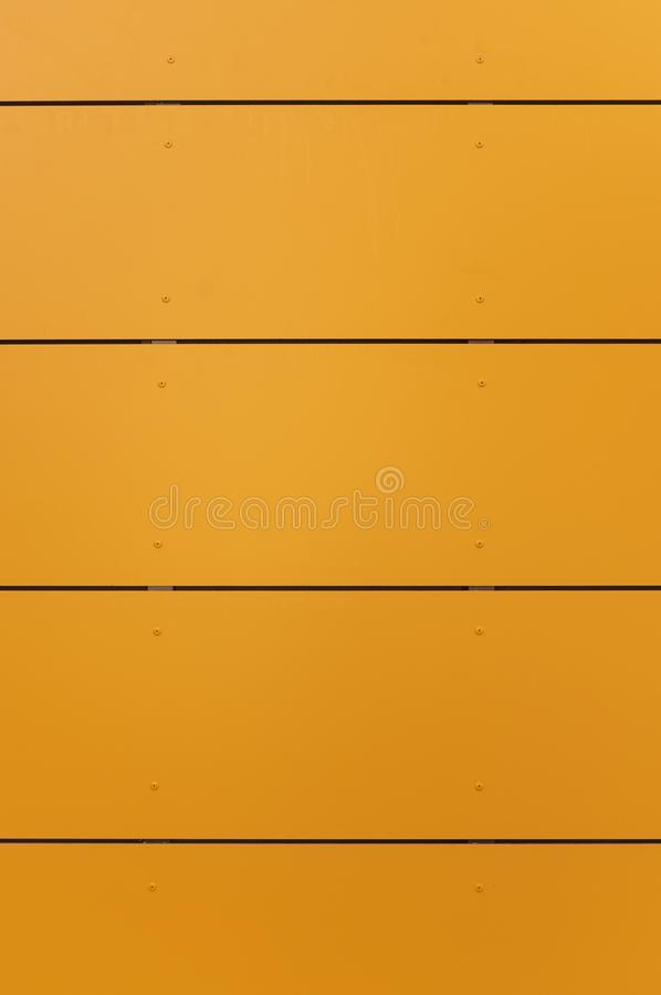 Modern facade with façade cladding and thermal insulation of yellow-orange elements, riveted to a substructure. In germany royalty free stock image