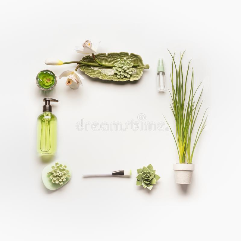 Herbal cosmetic concept. Frame of green cosmetic products, accessories, plants and orchid flowers on white desktop. Modern facial skin care setting . Herbal stock image