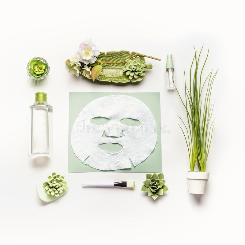 Modern facial skin care setting . Herbal cosmetic concept. Sheet mask with green cosmetic products royalty free stock photos