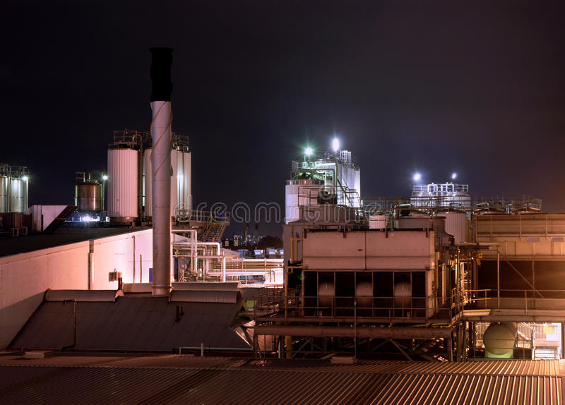 Modern factory industrial plant at night, stainless steel cooling tower and pipelines, copy space stock photography