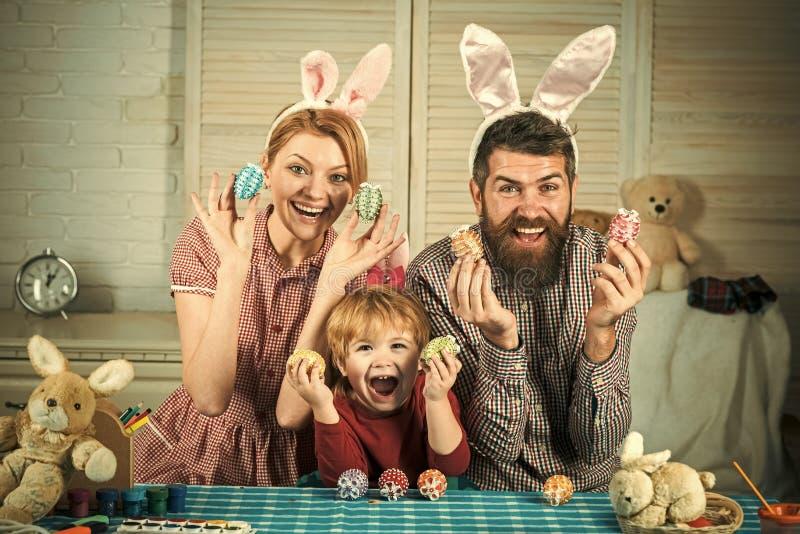 Modern, fadern och sonen målar ägg arkivfoton