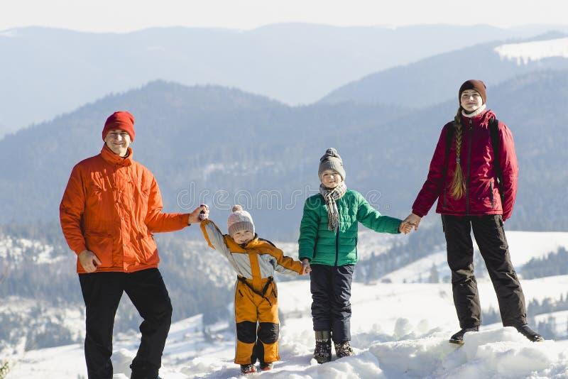 Modern, fadern och två söner är stå och le mot bakgrunden av snö-korkade berg lycklig familj Solig dag för vinter royaltyfri bild