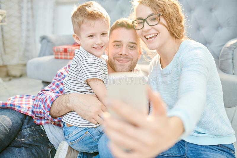 Modern Family Taking Selfie at Home. Warm toned portrait of loving young family with cute little son playfully taking selfie at home in sunlight royalty free stock photo