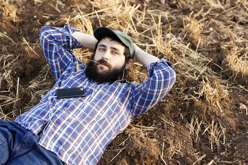 Modern farmer on a break. Laying on the ground and listening to music on his smartphone