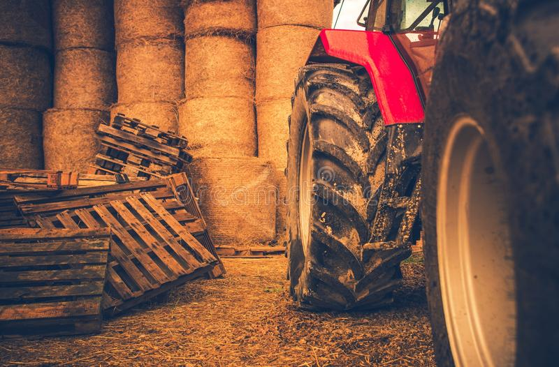 Modern Farming Equipment. Side of the Tractor and Hay Bales. Preparing Farm For the Winter royalty free stock photo