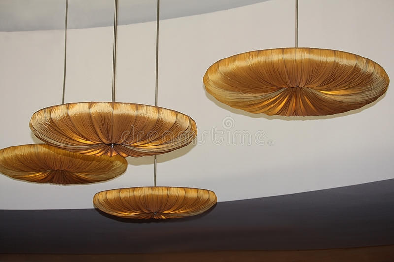 Modern fashion design ceiling. Round shape chandeliers with gold fabric upholstery. Modern fashion design ceiling. Beige yellow lights in the original stock photo