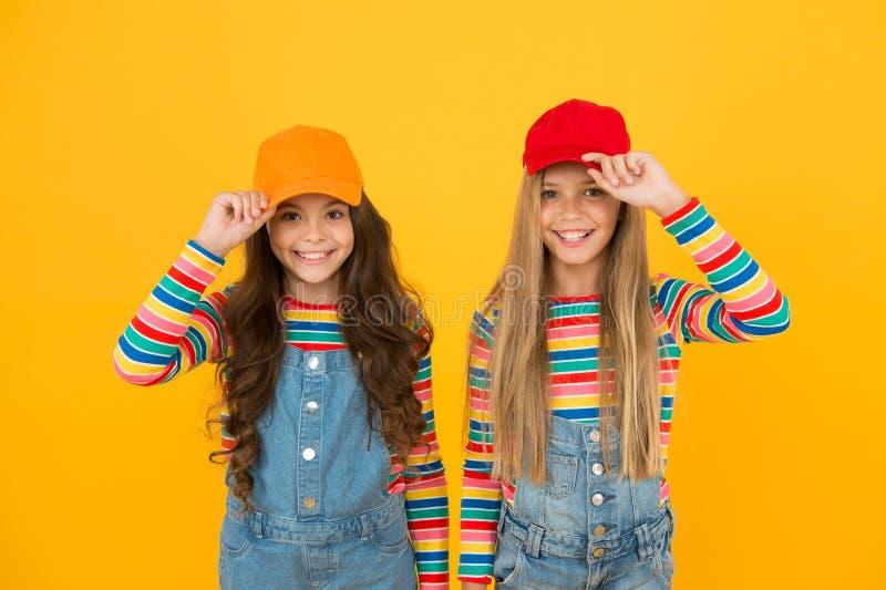 Modern fashion. Kids fashion. Girls long hair wear cap. Cute children wear cap snapback hat. Little girls wearing. Baseball cap. Matching outfits. Trendy and royalty free stock photos