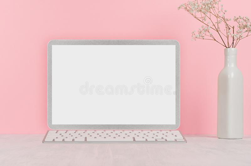 Modern fashion workplace - silver laptop with blank screen, white stationery on soft pink background. stock photo