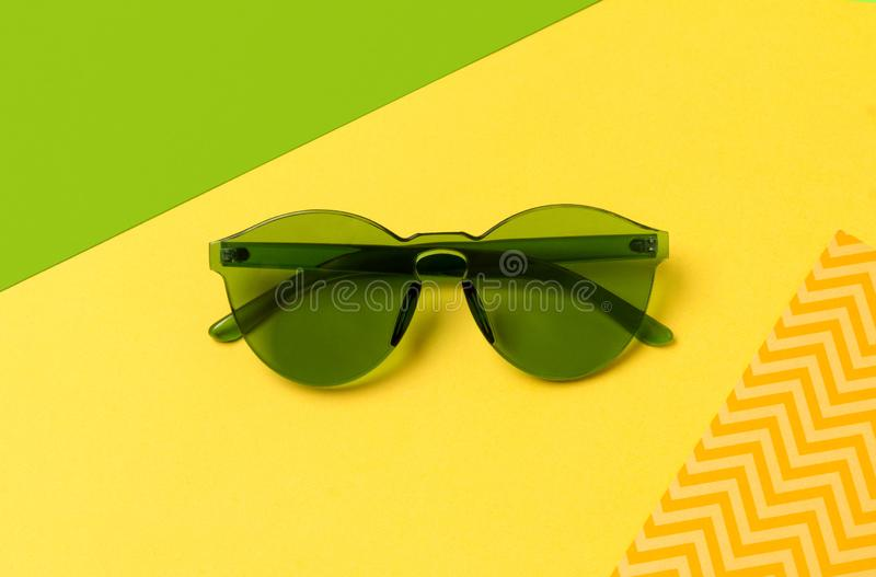Modern fashionable green sunglasses on creative yellow background stock photo