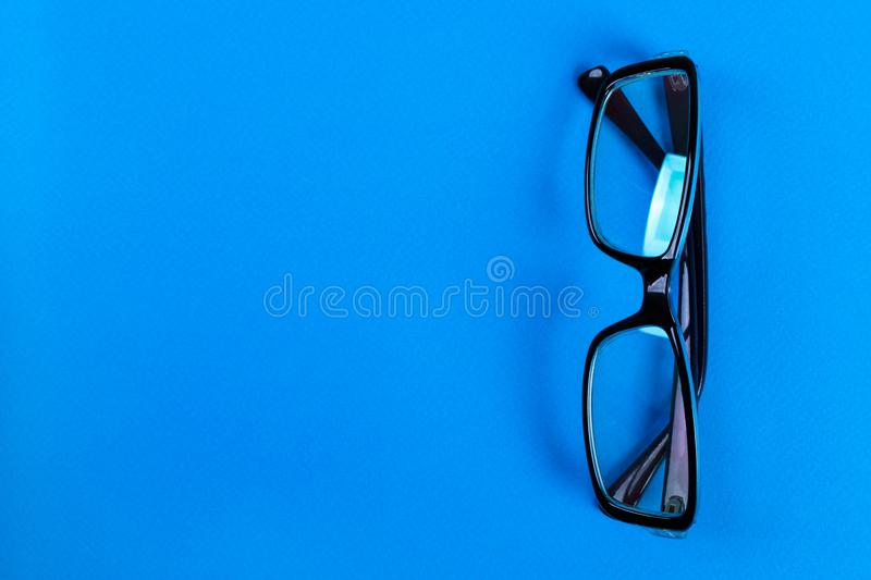 Modern fashionable and office spectacles on blue background, Perfect reflection, eye glasses on table for copy space stock image