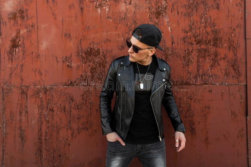Modern fashionable young hipster man with sunglasses in a stylish leather black jacket in a cap in a vintage T-shirt in gray jeans royalty free stock photography