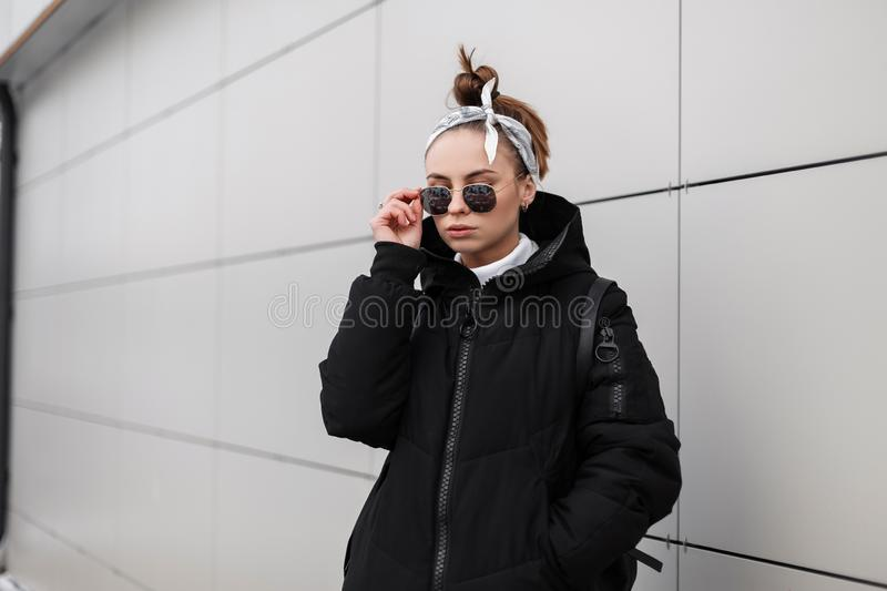 Modern fashionable young woman hipster with stylish hairstyle in black glasses in a stylish long black coat with a bandana. With a leather backpack on her stock photo
