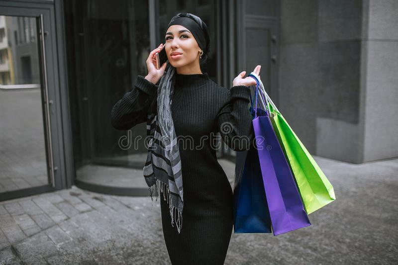 Modern and fashioned young arabian woman walks and talks on phone. She cary shopping bags behind shoulder. royalty free stock images