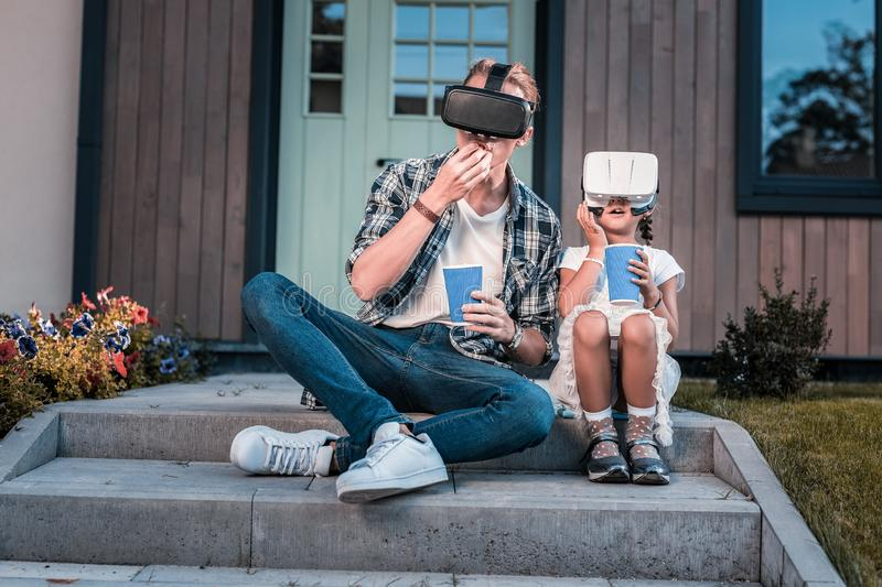 Modern father and daughter wearing virtual reality glasses sitting on the porch. Virtual reality. Modern father and daughter wearing virtual reality glasses royalty free stock photo