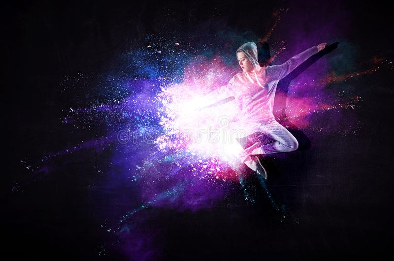 Modern female dancer jumping in hoodie with colourful splashes background. Mixed media royalty free illustration