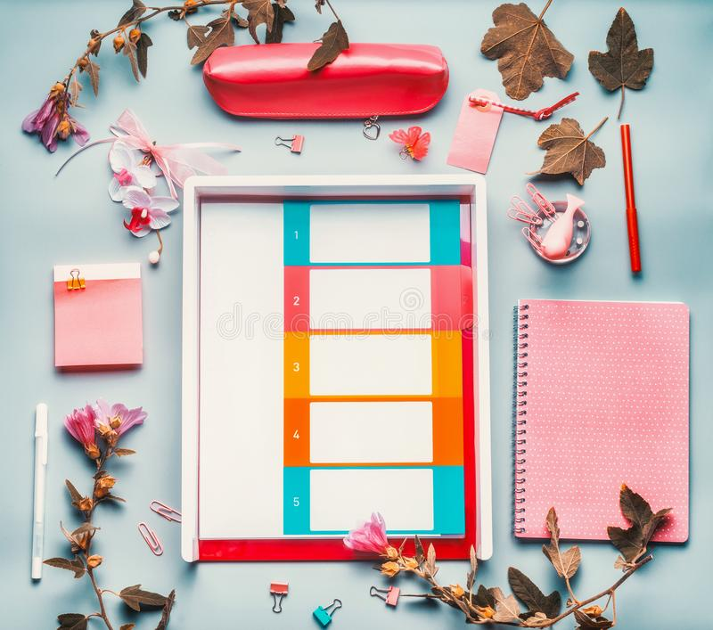 Modern female home office desktop in pink red color with flowers , accessories and planner wallet on blue background,top view. Fla royalty free stock photo