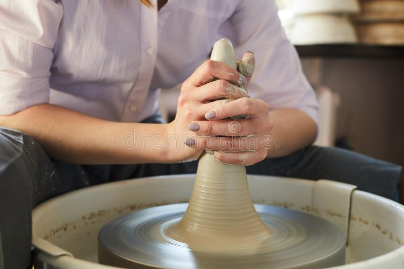 Modern Female Potter Closeup. Mid section closeup of female potter shaping clay on wheel while working in studio, copy space stock image