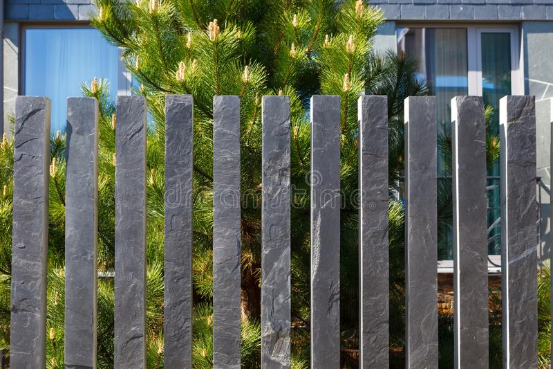 Modern fence made of bars pillars of gray, mountain, Silesian slate.  stock photos