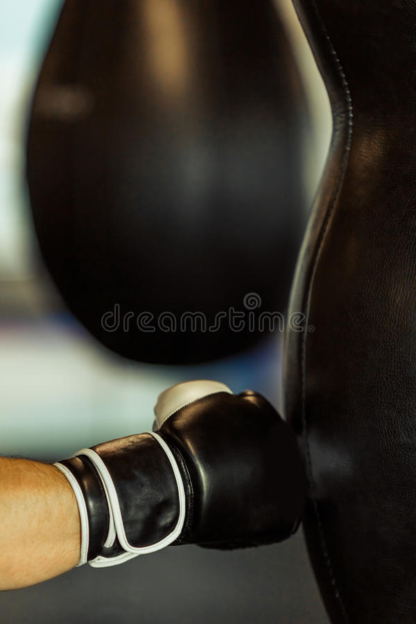 Modern fight club. Boxer in boxing gloves practising with punching bag in a fight club, close-up royalty free stock images