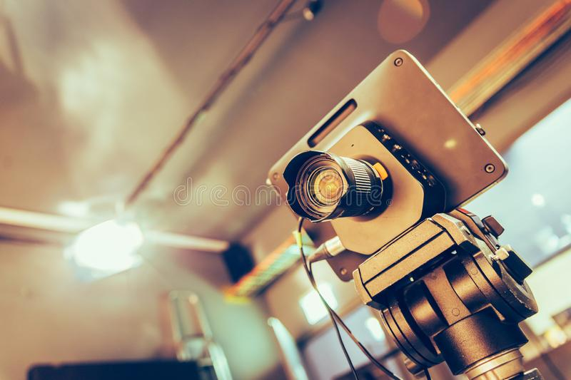 Modern film camera on a tripod in a broadcasting studio, spotlights and other equipment. Film camera on a tripod in a television broadcasting studio, spotlights royalty free stock images