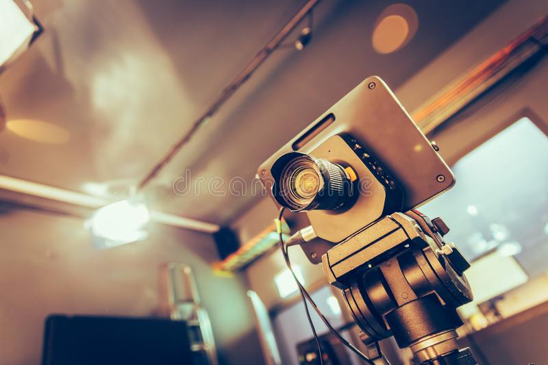 Modern film camera on a tripod in a broadcasting studio, spotlights and other equipment. Film camera on a tripod in a television broadcasting studio, spotlights stock photo