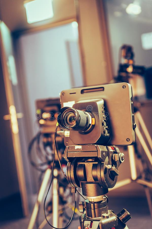 Modern film camera on a tripod in a broadcasting studio, spotlights and other equipment. Film camera on a tripod in a television broadcasting studio, spotlights stock image