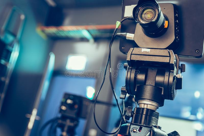 Modern film camera on a tripod in a broadcasting studio, spotlights and other equipment. Film camera on a tripod in a television broadcasting studio, spotlights stock images