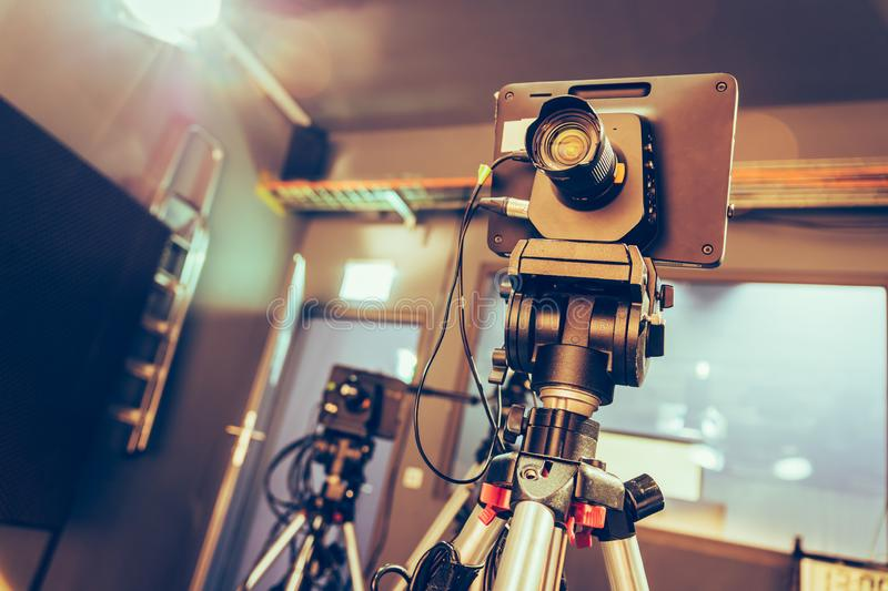 Modern film camera on a tripod in a broadcasting studio, spotlights and other equipment. Film camera on a tripod in a television broadcasting studio, spotlights royalty free stock photography