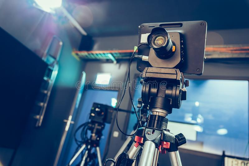 Modern film camera on a tripod in a broadcasting studio, spotlights and other equipment. Film camera on a tripod in a television broadcasting studio, spotlights royalty free stock photos