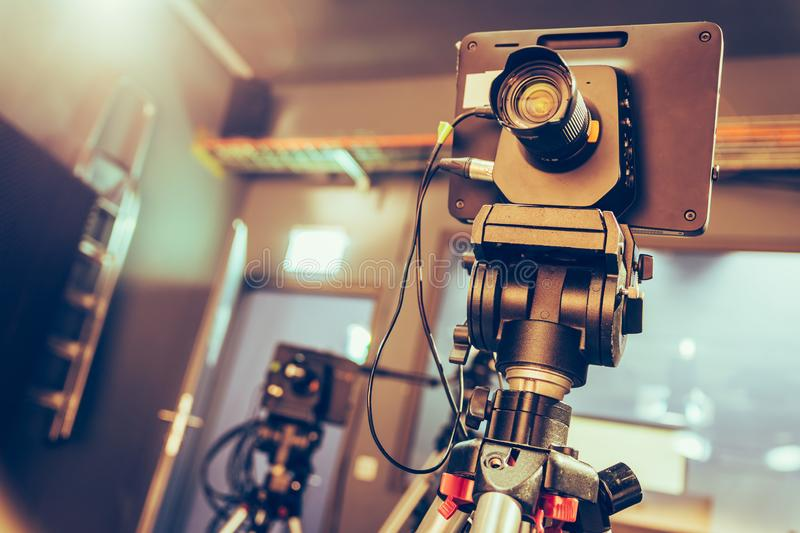 Modern film camera on a tripod in a broadcasting studio, spotlights and other equipment. Film camera on a tripod in a television broadcasting studio, spotlights royalty free stock image