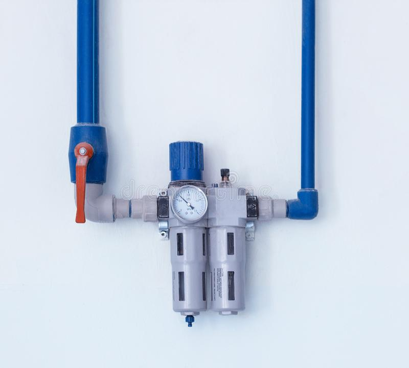 A modern filter with a water gauge for cleaning from debris and heavy metals, located on the wall, a water pipe water purification stock photo