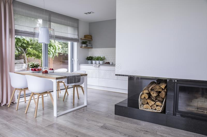 Modern fireplace and wood in a spacious dining room interior wit. H white chairs by a wooden table and big windows Concept stock photo