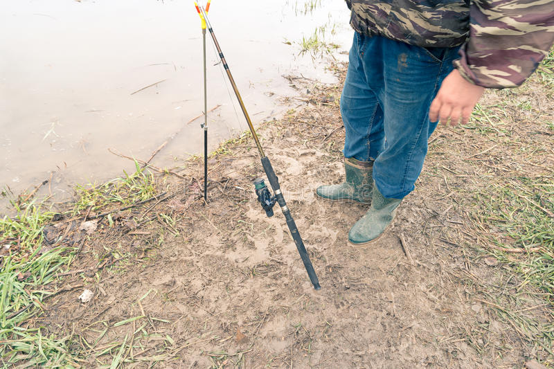 Modern fishing rod outdoors on the ground and fishermans legs above view.  stock image