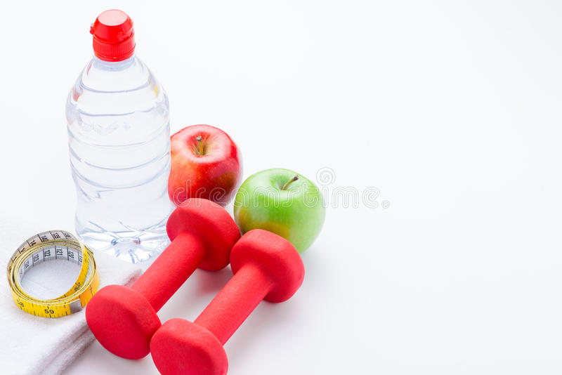 Modern fitness and gym workout concept. Healthy lifestyle background with blank copy space dumbbells, measure tape, fruits and wat stock photography