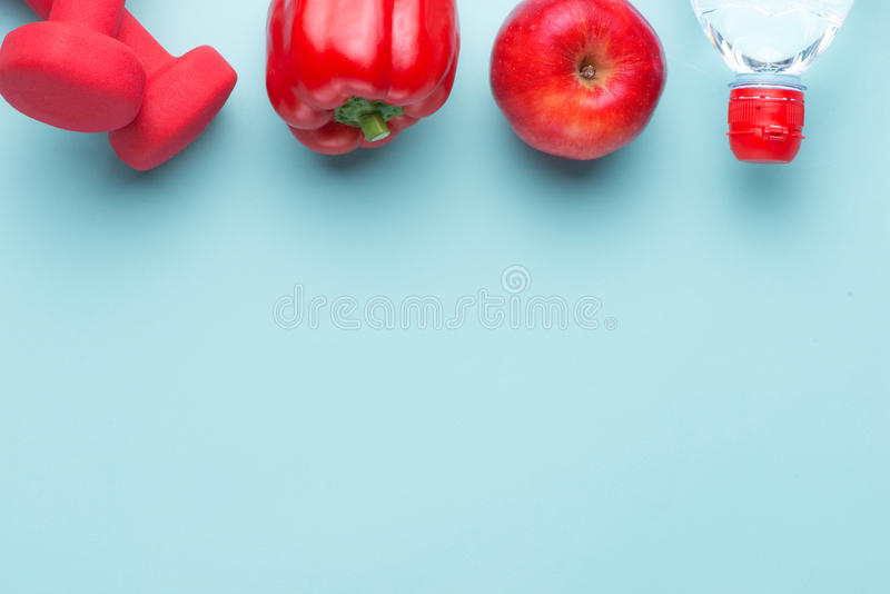 Modern fitness healthy sport gym woman with copy space. Top view angle. Dumbbells, red apple, bell pepper and water bottle close royalty free stock images