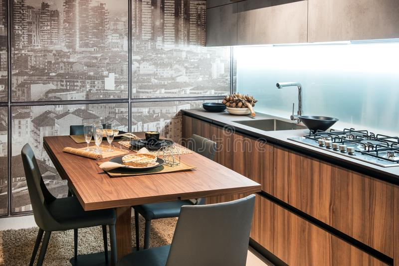 Modern fitted kitchen with table and glass wall. Modern fitted kitchen with wooden cabinets, sink, dining table laid with dinnerware and glass wall overlooking royalty free stock photography
