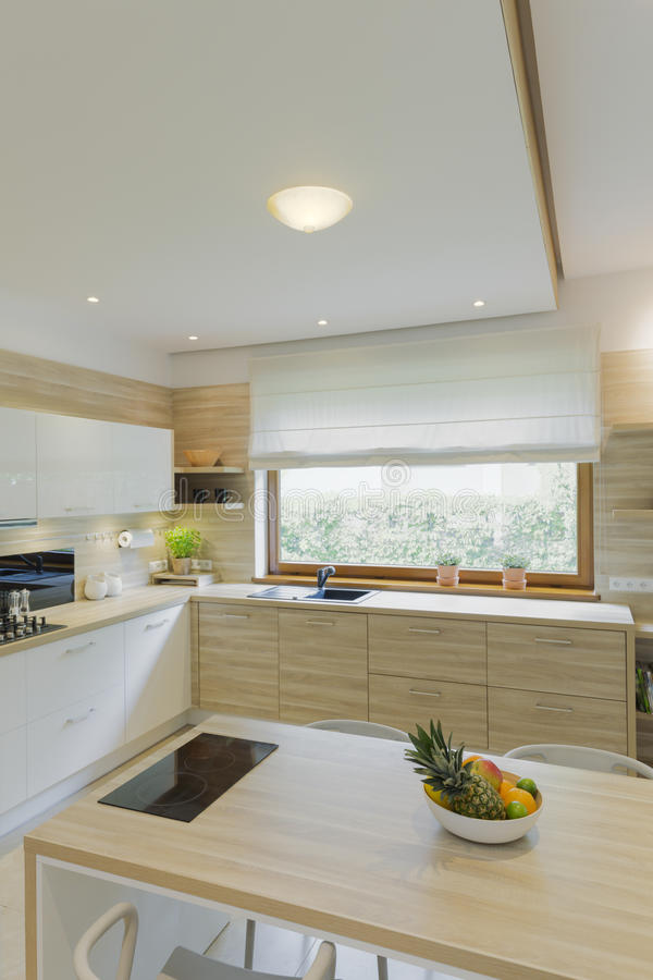 Modern fitted kitchen with window. Fitted white wooden kitchen with wide window, minimalist cabinets, island and dropped ceiling royalty free stock image
