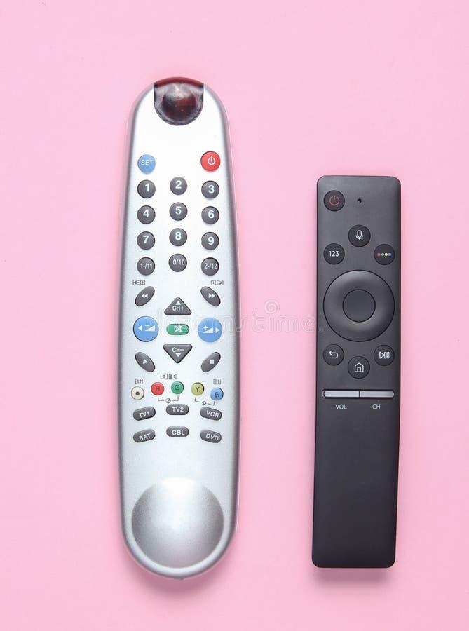 Modern fjärrkontroll för tv två på en rosa pastellfärgad bakgrund Bästa sikt, minimalism arkivfoto