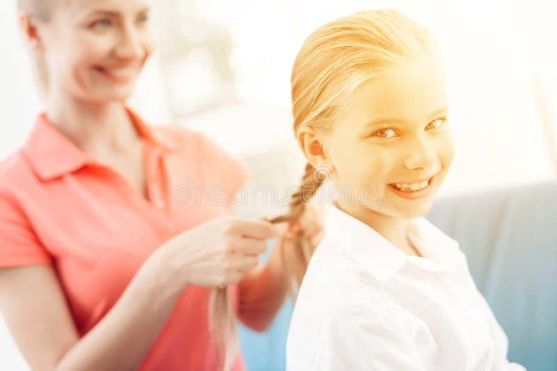 Modern flätar hennes hår för dotter` s En kvinna flätar en flicka för flätad tråd lite royaltyfri bild