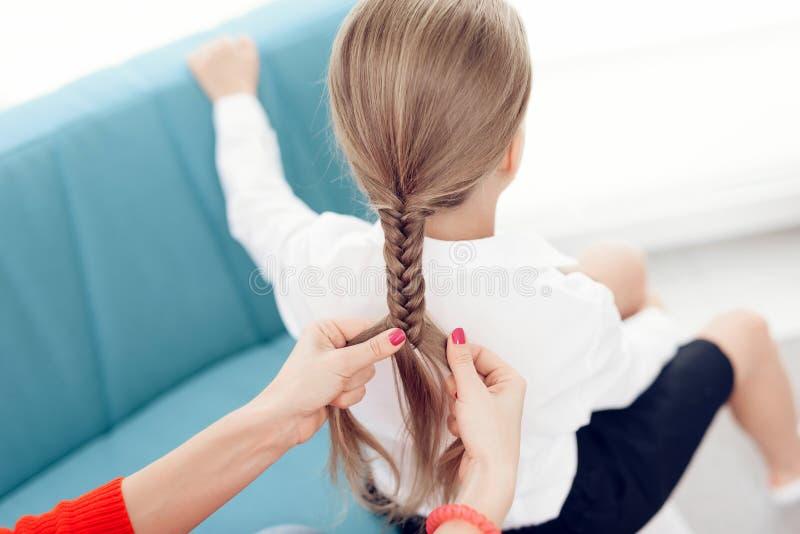 Modern flätar hennes hår för dotter` s En kvinna flätar en flicka för flätad tråd lite arkivbilder
