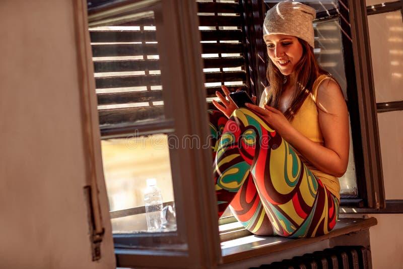 Modern folkstadslivsstil Stads- kvinna som använder telefonen och textin royaltyfria foton