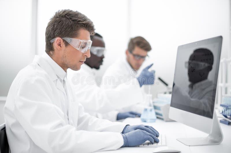 Modern forskare som använder en dator för dataanalys royaltyfri bild