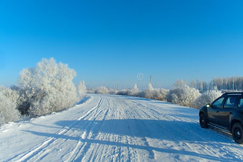 Modern four-wheel drive car on the snowy rural road stock photos