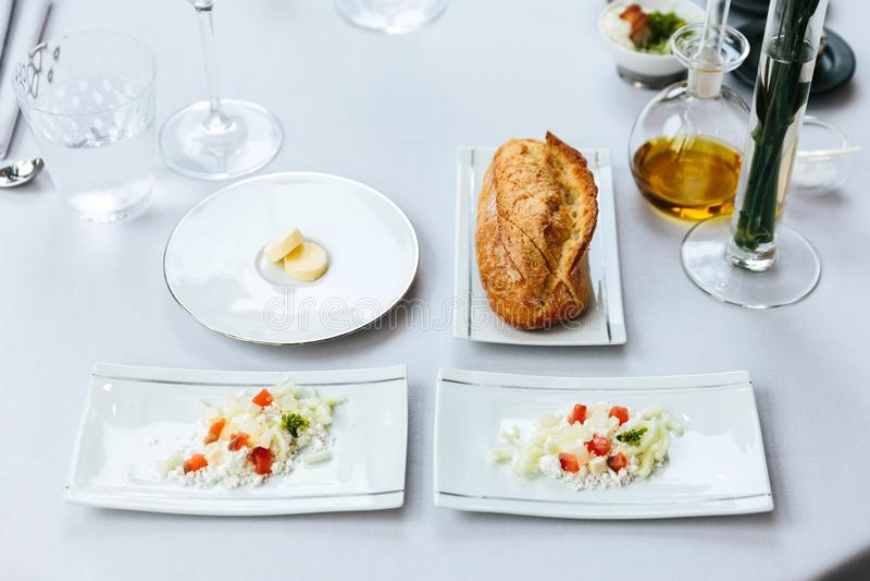 Modern Frans voorgerecht: Het verse gebakken brood van brood met boter en verbrijzeling en besnoeiingskaas met gedobbelde tomaat  stock fotografie