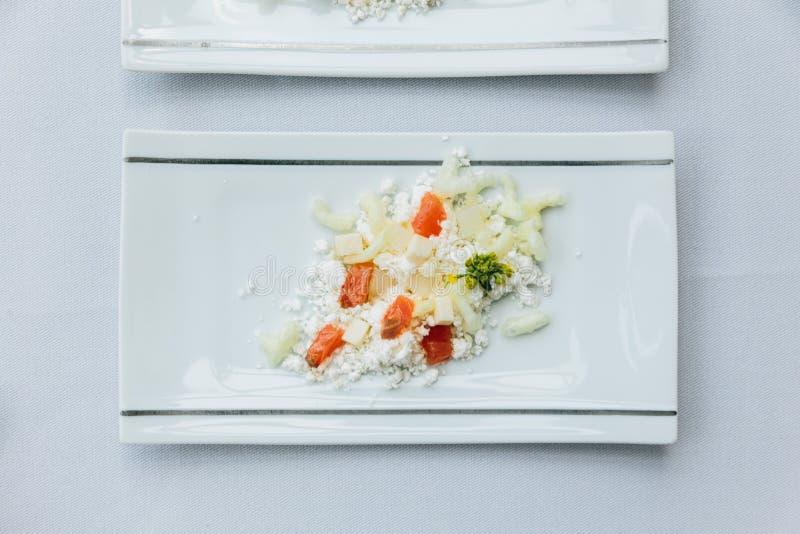 Modern fransk aptitretare: krossa och klipp ost med den tärnade tomaten som tjänas som på den vita rektangelplattan fotografering för bildbyråer