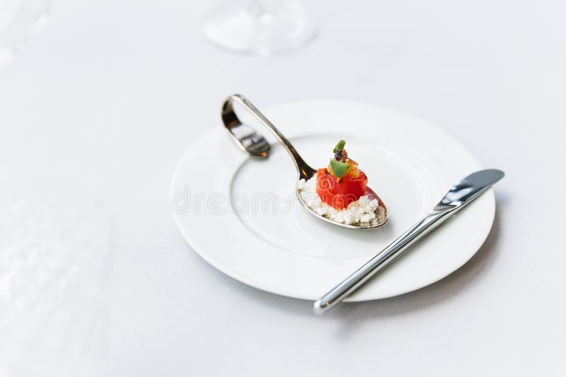 Modern French food: Diced watermelon with white crush cheese served in silver spoon on white plate with cutlery as appetizer.  stock photos