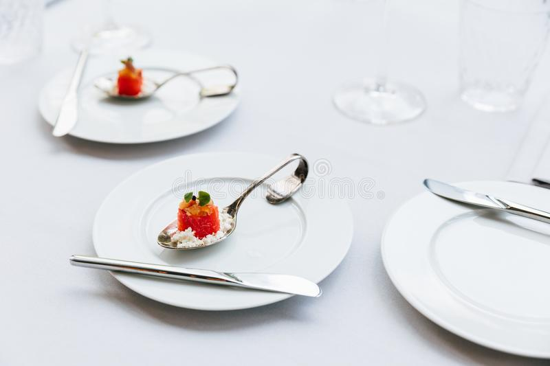Modern French food: Diced watermelon with white crush cheese served in silver spoon on white plate with cutlery as appetizer.  stock image