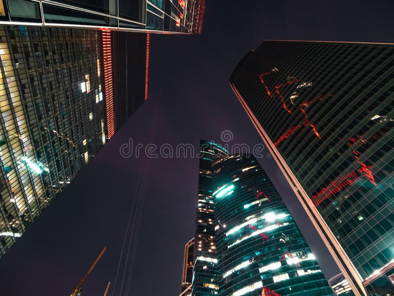 Modern futuristic skyscrapers buildings in business center in Moscow city at night with illuminated windows and lights. Toned stock photo
