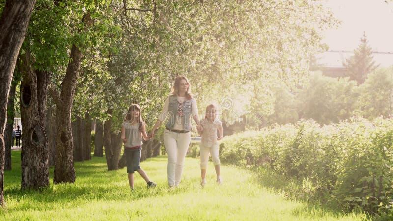 Modern går med hennes döttrar längs avenyn av äppleträd Lilla flickan rymmer hennes moder vid handen